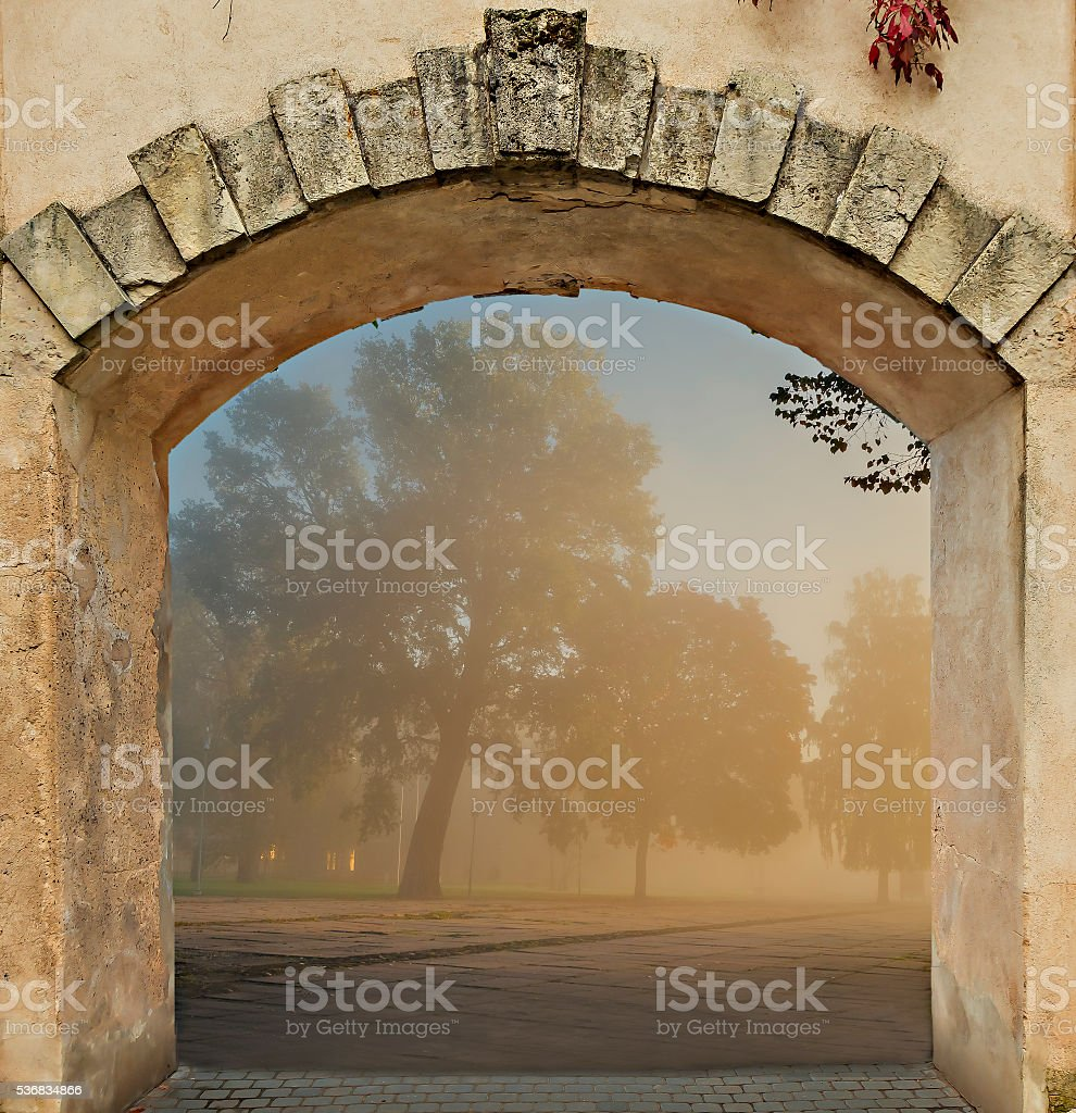 View on autumnal park through medieval arch stock photo