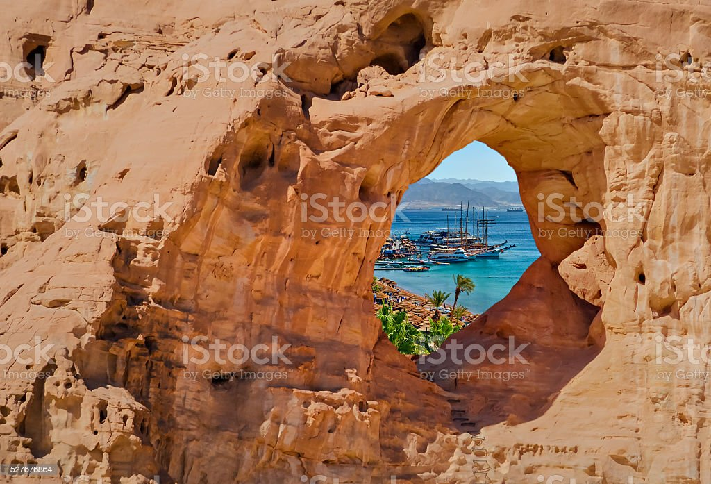 View on marina of Eilat through arch of sandstone stock photo