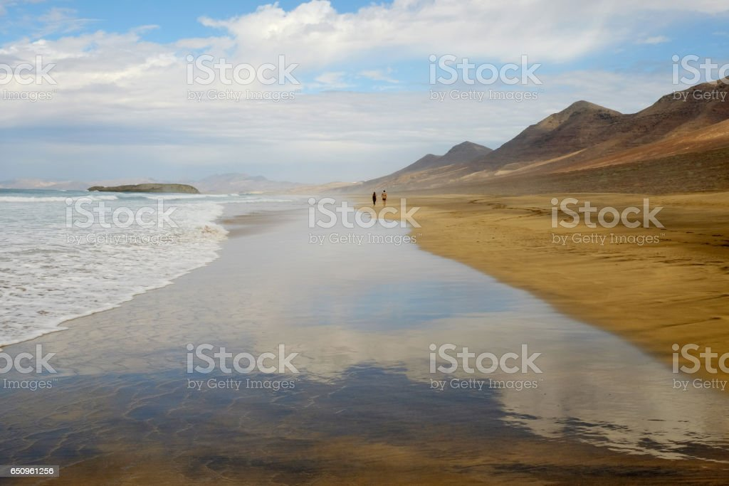 View on the beach Cofete with two unknown walking persons far away on Fuerteventura, Spain. stock photo