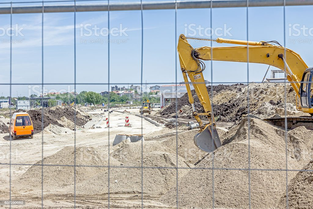 View on the construction site through a fence wire excavator. stock photo