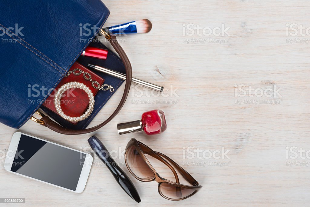 View on women bag stuff with copyspace on wooden background stock photo