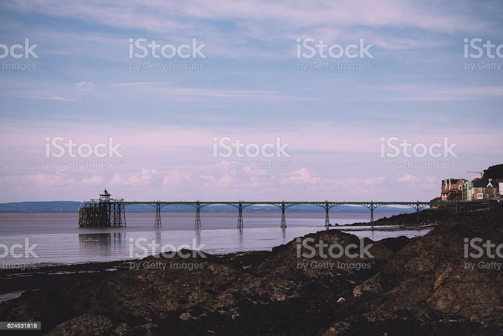 View over rocks at Clevedon sea front, including pier in stock photo
