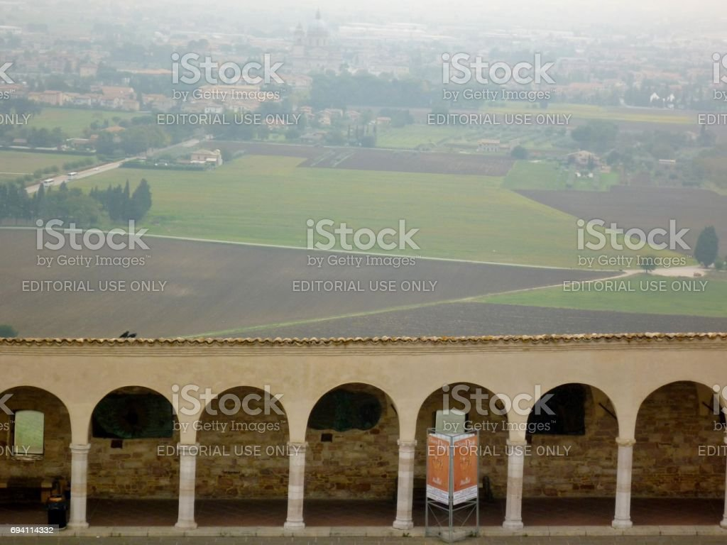 View over the covered arcade of the 'Lower Square of St Francis' in Assisi, Italy, with the Basilica of Santa Maria degli Angeli visible in the far distance stock photo