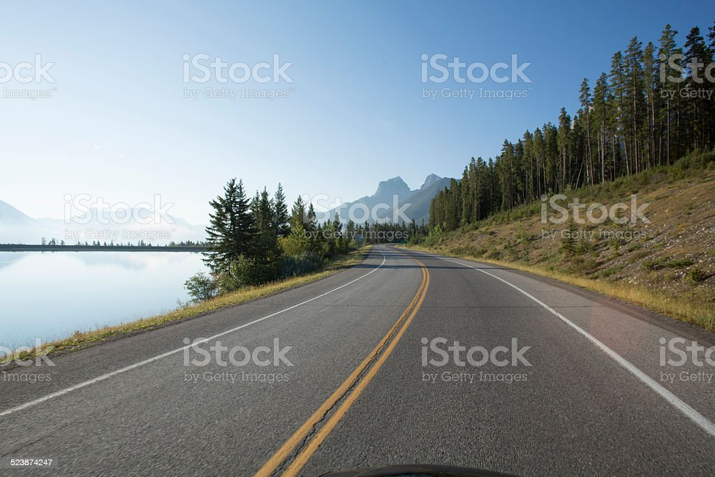 View past car hood to mountain road, lake stock photo