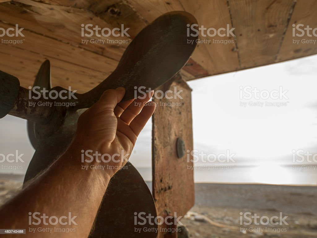 View past man's hand checking propeller blade, to sea stock photo