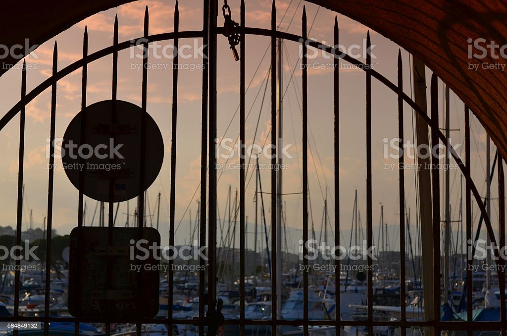 view  through a metal gate at the evening stock photo