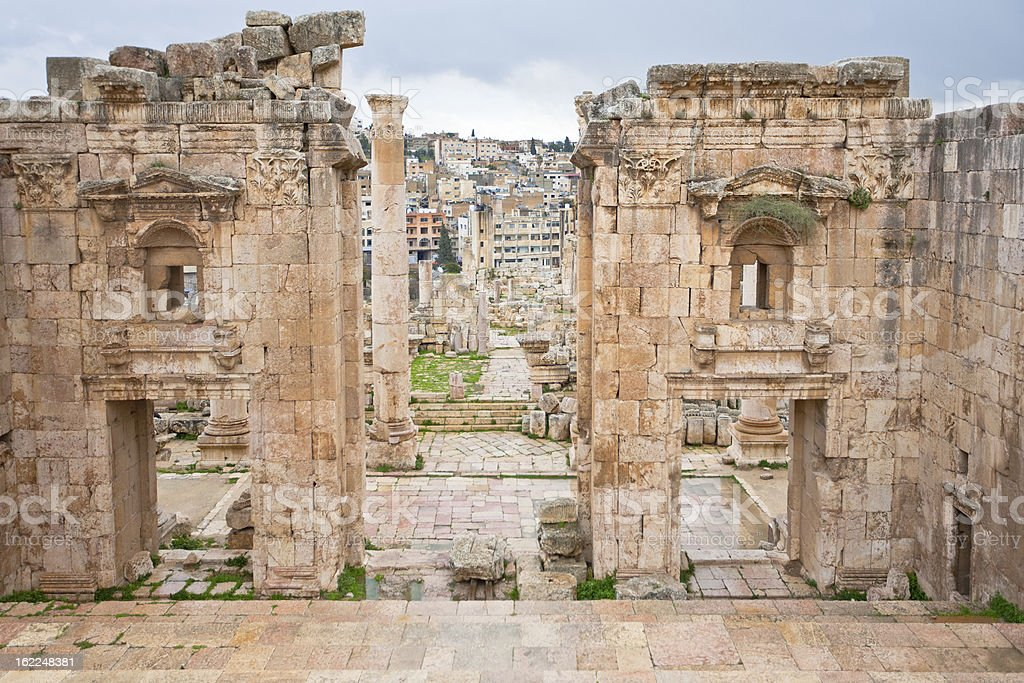 view through antique Artemis temple  to modern Jerash stock photo