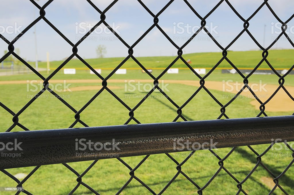 View through Fence of Baseball Field from Dugout Bench royalty-free stock photo