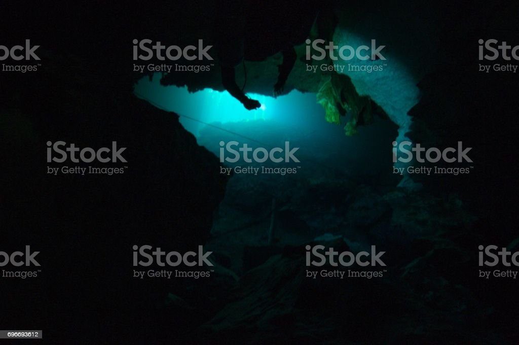 view through rock formation inside cave diving cenotes stock photo