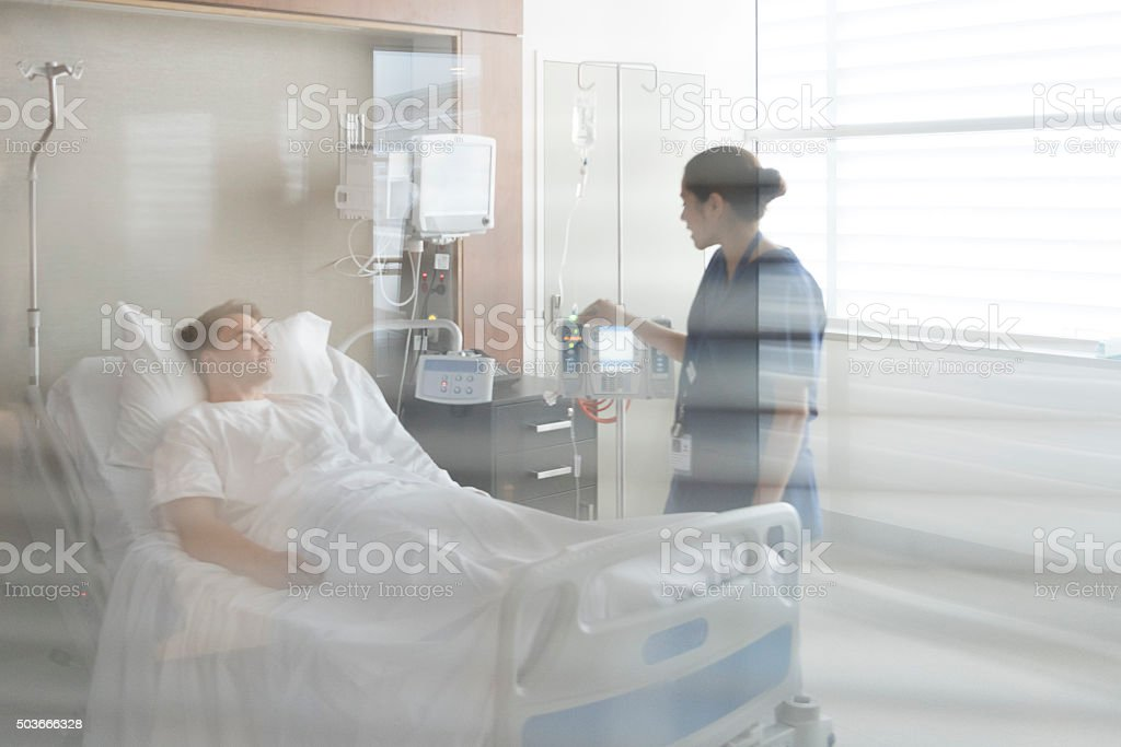 View through window, patient in hospital bed with nurse stock photo