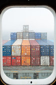View throught the porthole of a container ship