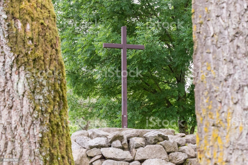 View to a wooden cross between two tree trunks stock photo