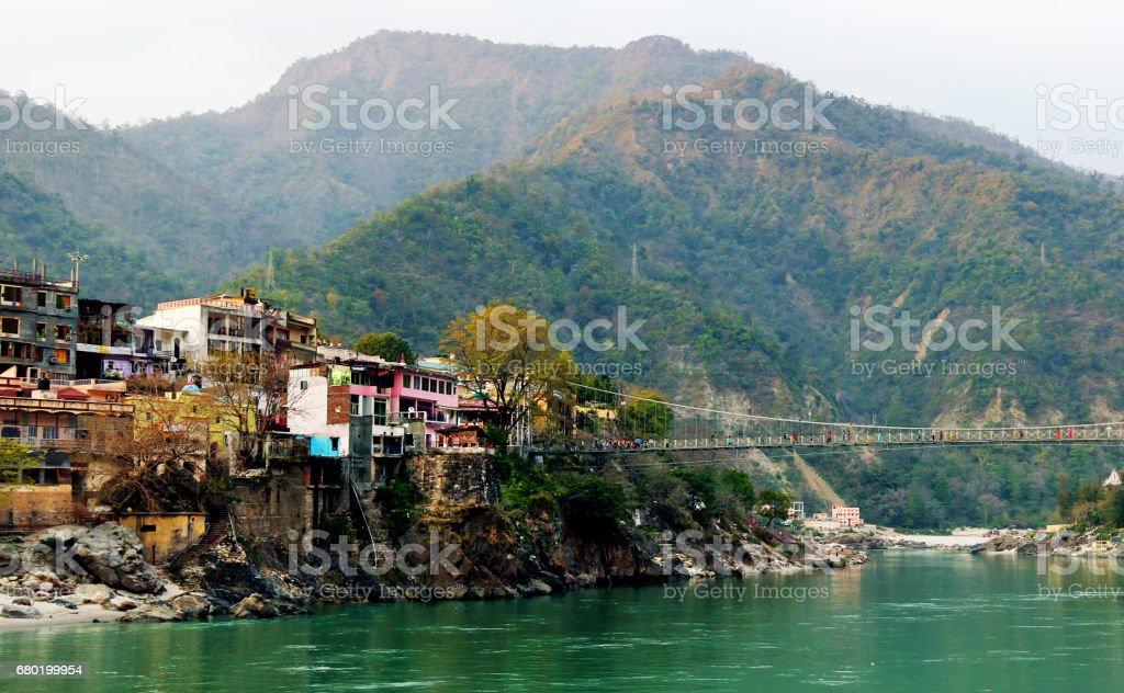 RISHIKESH, INDIA - view to Ganga river, lakshman jhula bridge and colored houses stock photo
