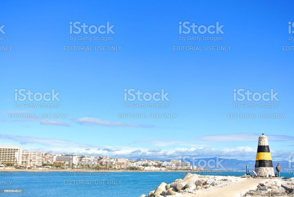 TORREMOLINOS, SPAIN - FEBRUARY 13, 2014: A view to Mediterranean sea, a lighthouse with breakwaters and Torremolinos at the background from a pier at Benalmadena port Puerto Marina, Andalusia, Spain. stock photo