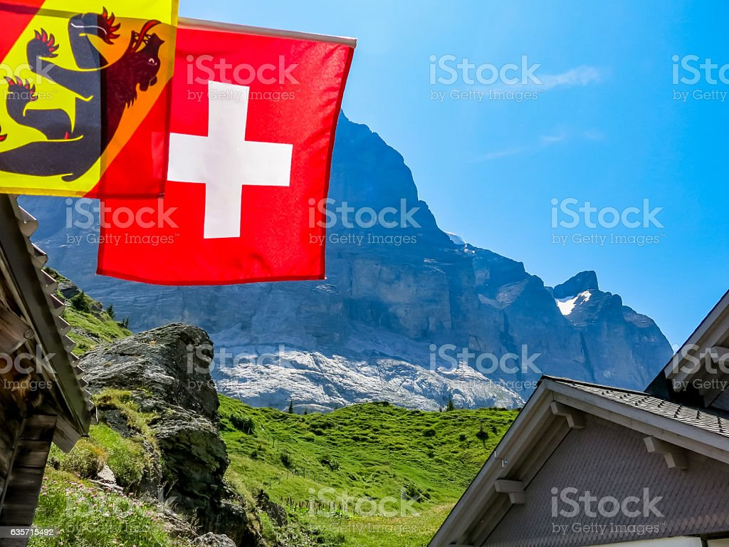 View up to eiger with foreground swiss flag stock photo
