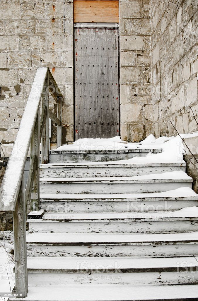 View Up Wooden Snow Covered Steps to Boarded Up Door stock photo