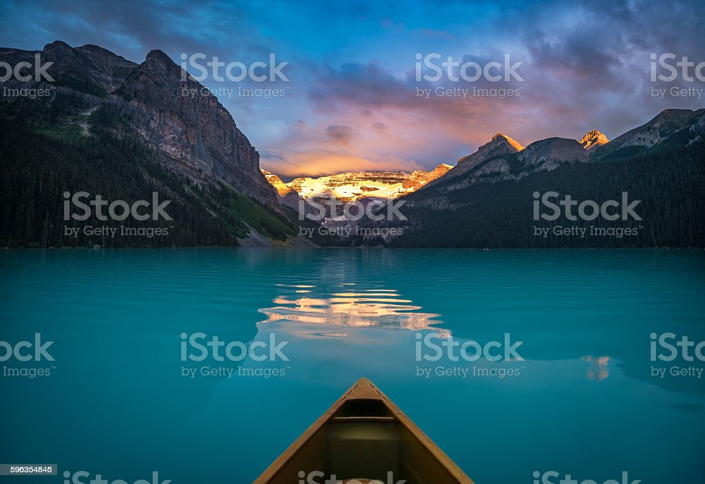 Viewing snowy mountain in rising sun from a canoe stock photo