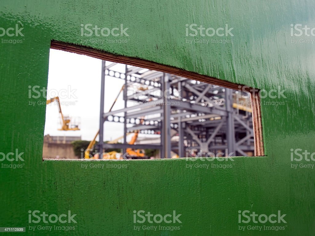 Viewing window hole in construction site hoarding stock photo