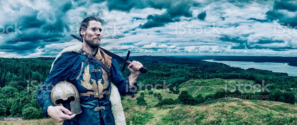 Viking warrior stands on hill overlooking the landscape stock photo