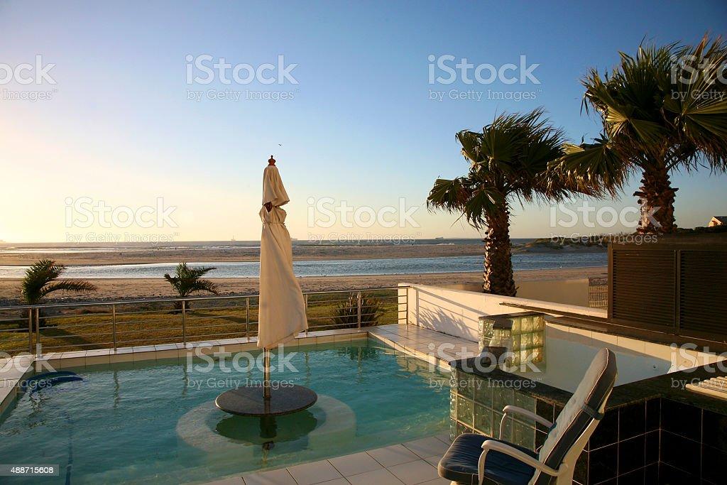 Villa on the beach with clear blue sky and ocean stock photo
