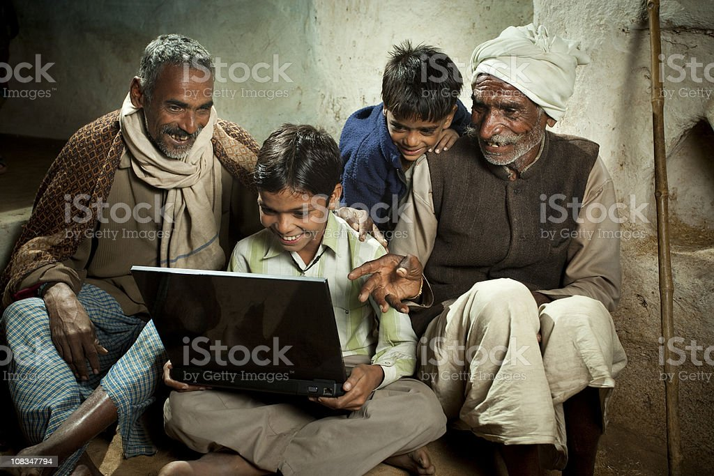 Village boy with father, grandfather and brother using a laptop stock photo
