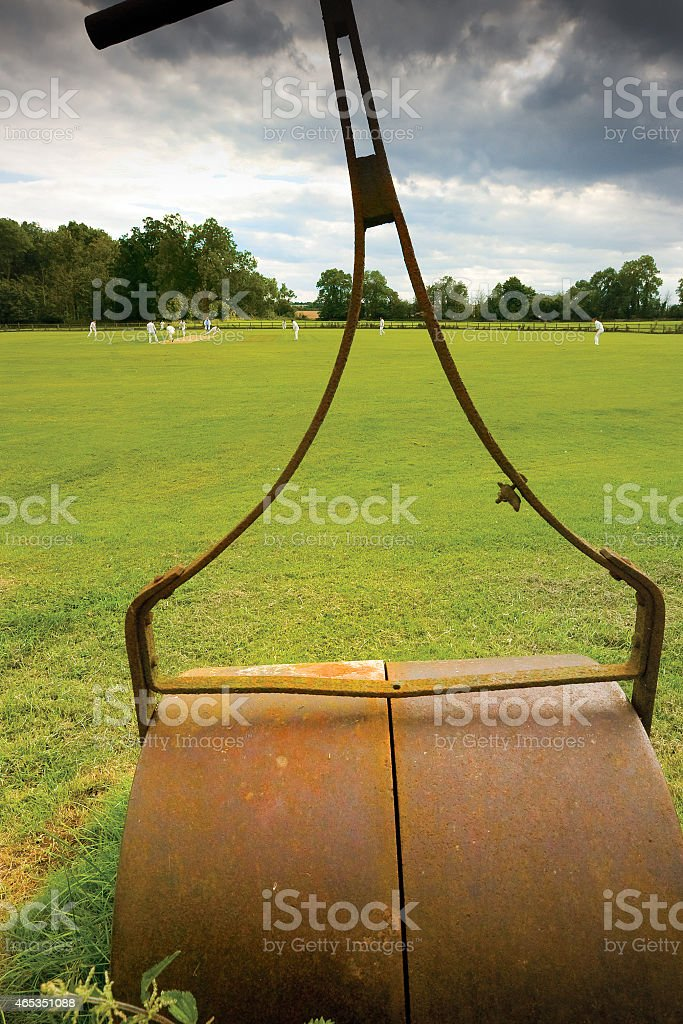 Village cricket match viewed through an old roller stock photo