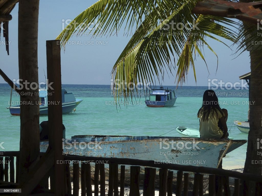 Village girl looking out on the sea stock photo