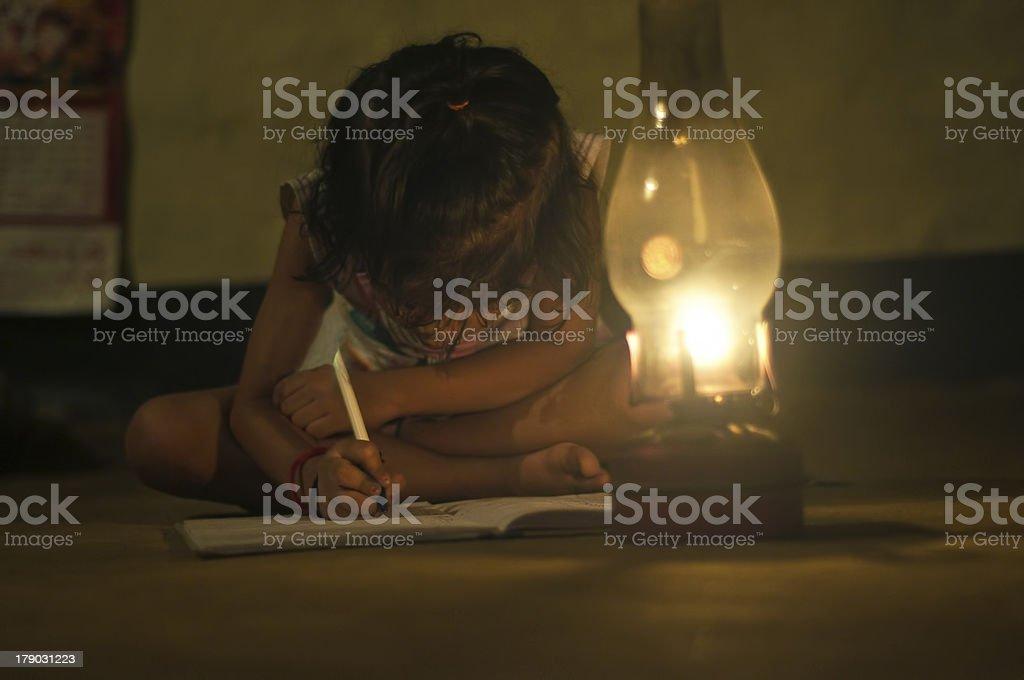 Village Girl reading book in lighting lamp stock photo