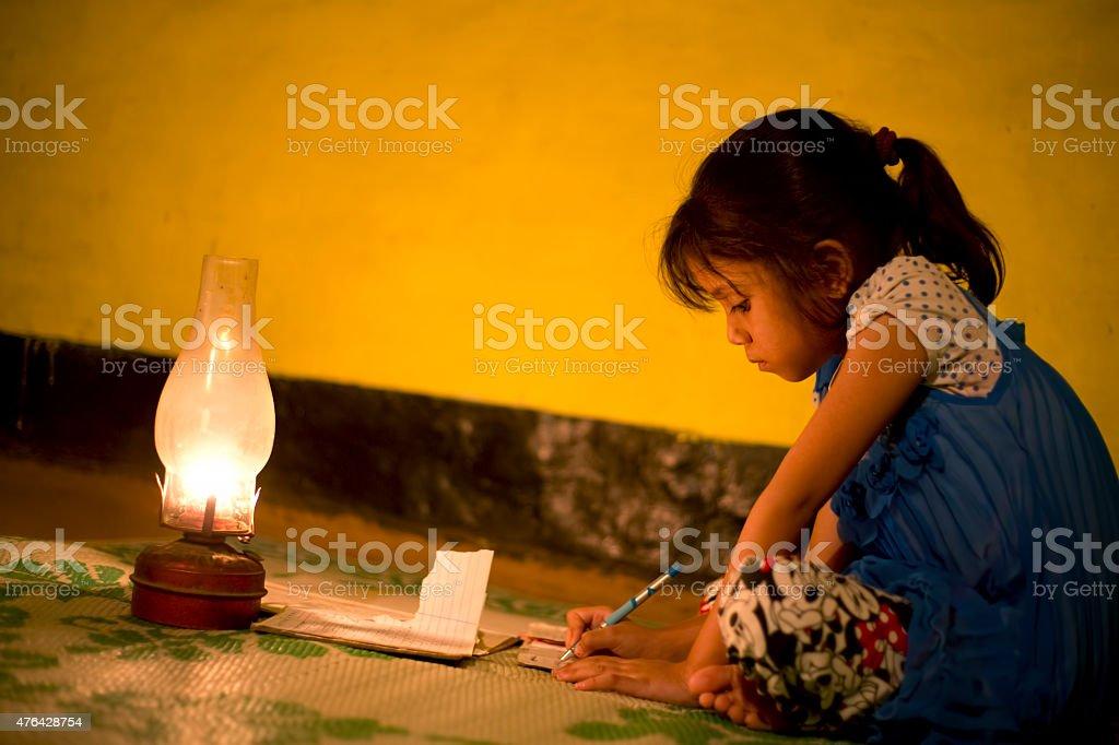 Village Girl studying in lighting lamp stock photo