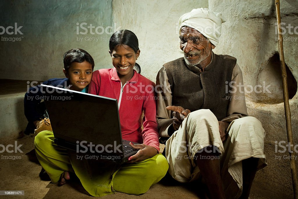 Village girl with brother showing laptop to her grandfather royalty-free stock photo