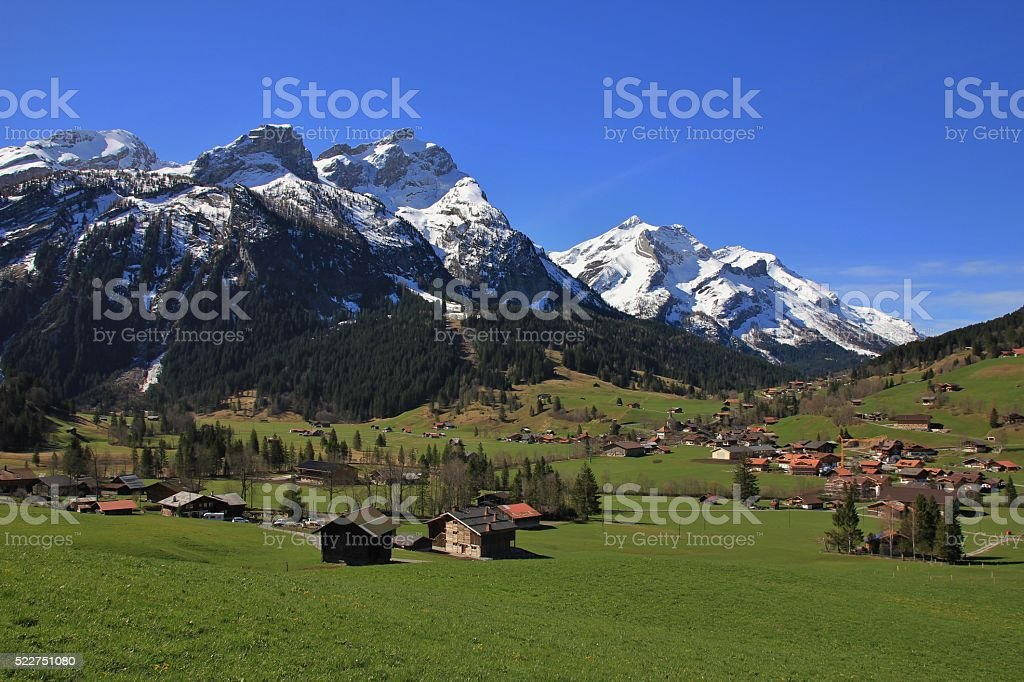 Village Gsteig bei Gstaad and snow capped mountains stock photo