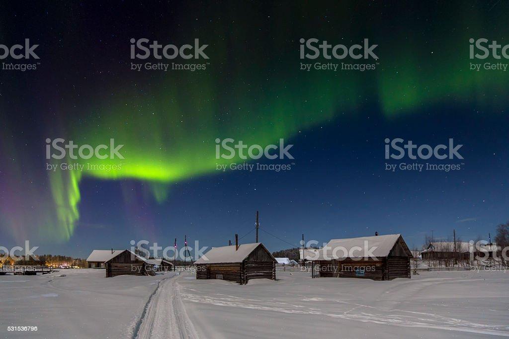 Village house in the lights of Aurora borealis. stock photo