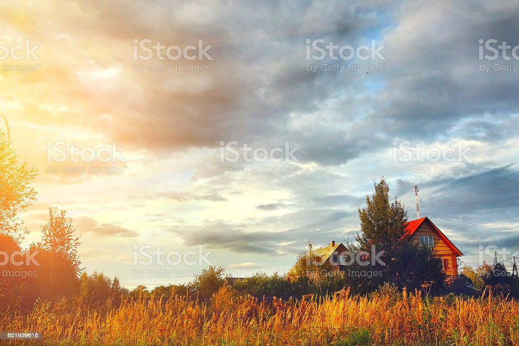village house on field and cloudy sky stock photo