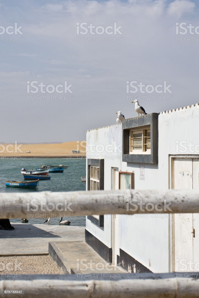 Village in sandy desert close to the cliffs. Perfect place to see tropical desert, wide cliffs and coloful beaches on the rocky islands and national reserve. Small islands near the town of Paracas. stock photo