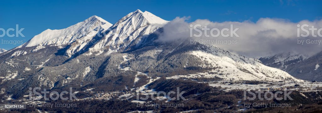 Village of Saint-Leger-les-Melezes in the Champsaur Valley in winter with snow covered Autane peaks. Alps, France stock photo