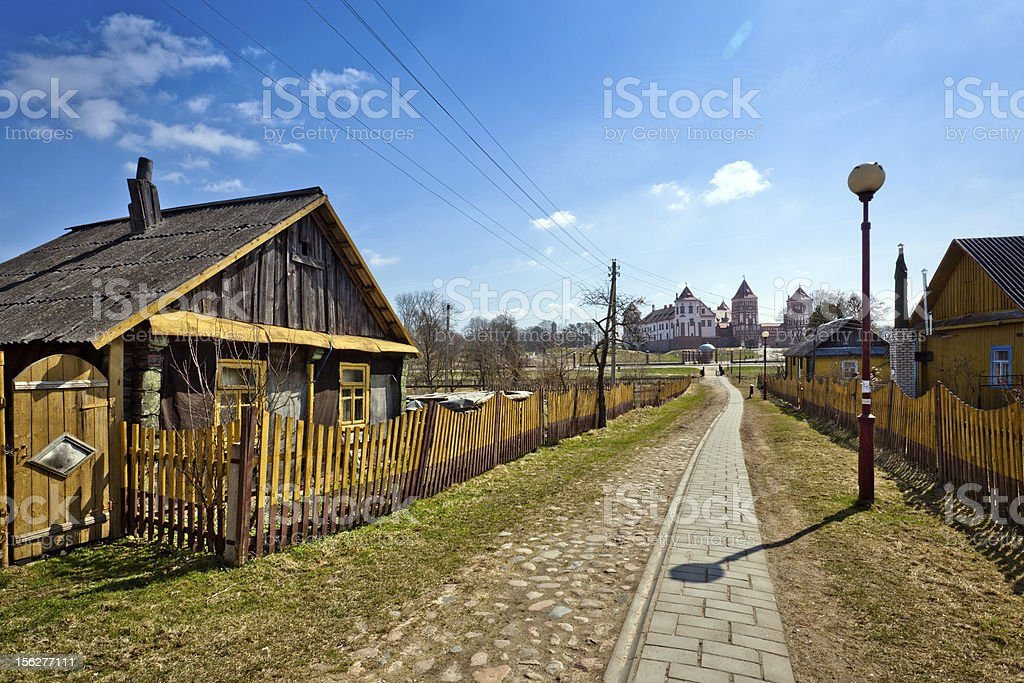 Village street and Mir castle on horizon stock photo