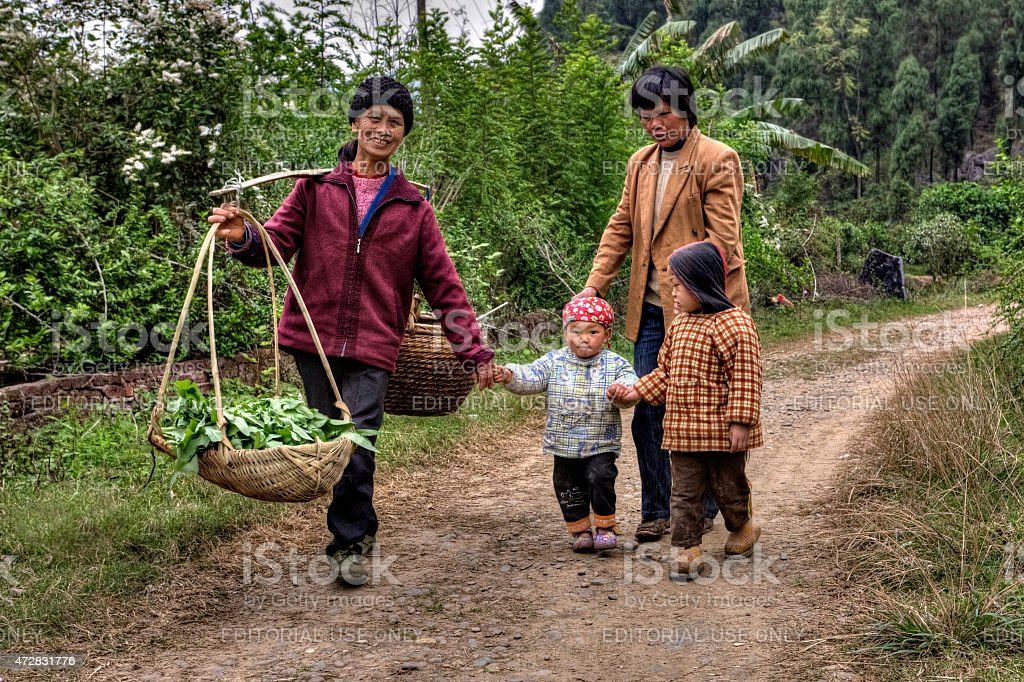 Villagers in China, women with children, are on country road. stock photo