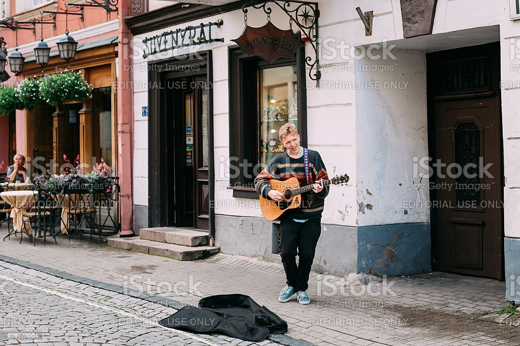 Vilnius Lithuania. Young Guy Street Musician Playing Guitar, Singing stock photo