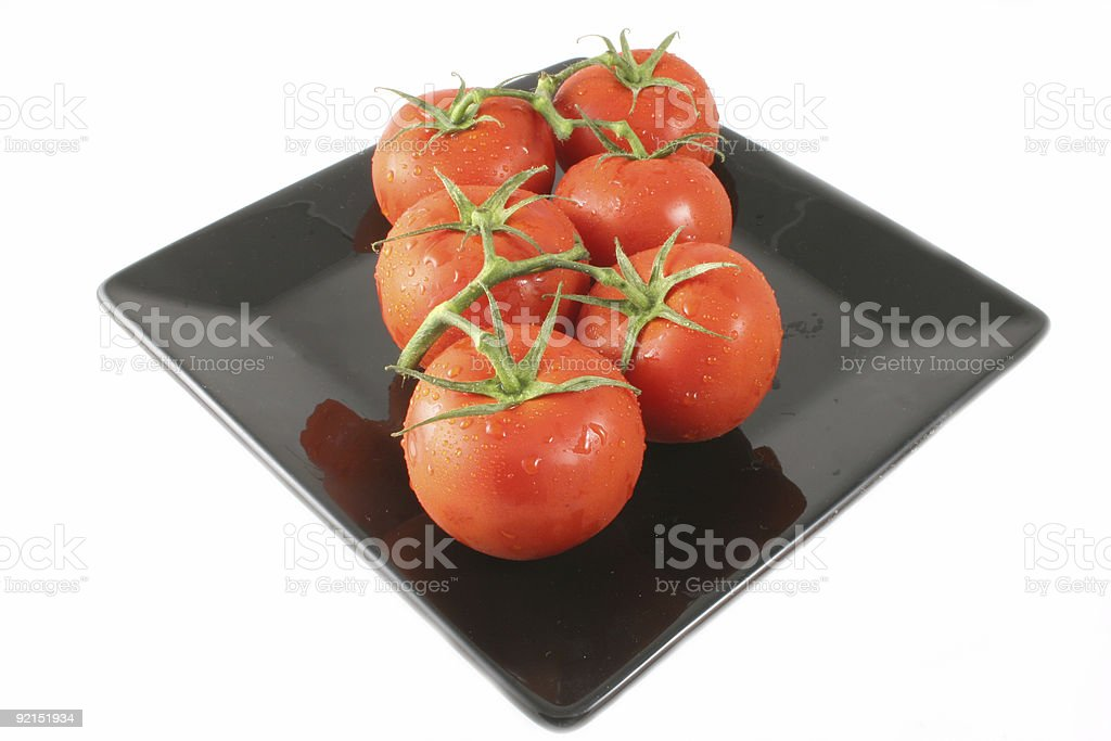 Vine Tomatoes Isolated on a black plate stock photo