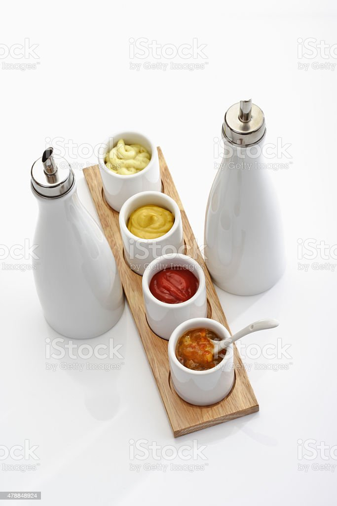 Vinegar and oil stand and bowls with different dips stock photo