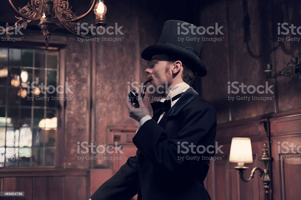 Vintage 1900 fashion man with beard. Smoking tobacco pipe. stock photo
