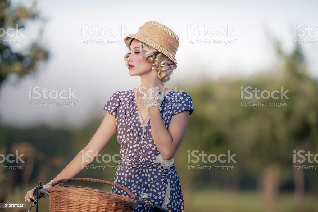Vintage 1930s fashion woman in blue dress standing with bicycle. stock photo