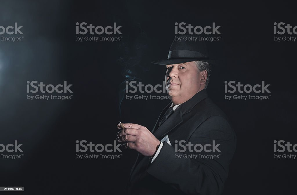 Vintage 1930s gangster holding cigar. Classic studio portrait. stock photo