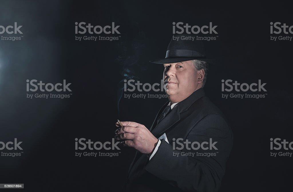 Vintage 1930s gangster holding cigar. Classic studio portrait. stock photo