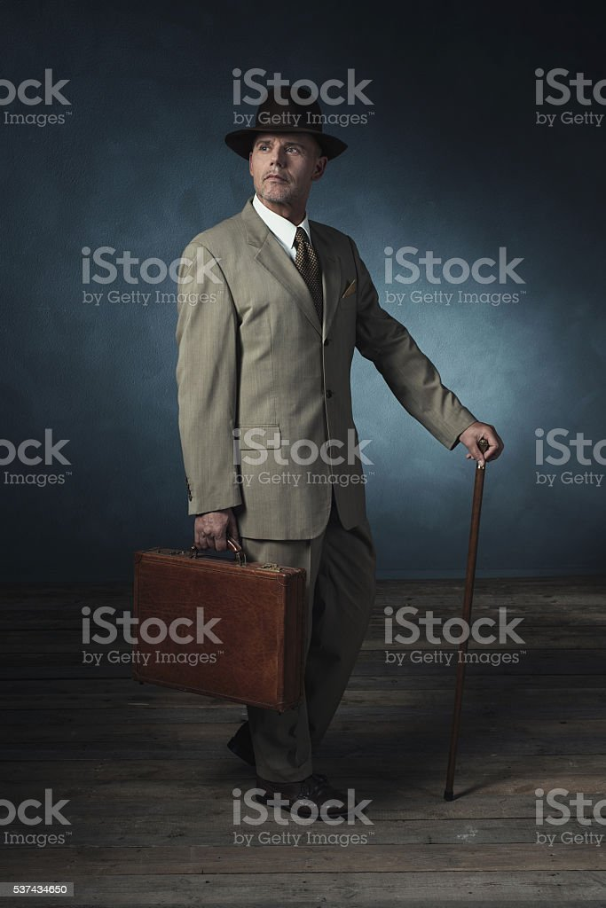 Vintage 1940 office worker standing with briefcase and cane. stock photo