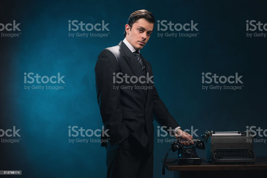 Vintage 1940s business man in suit hanging up the phone. stock photo