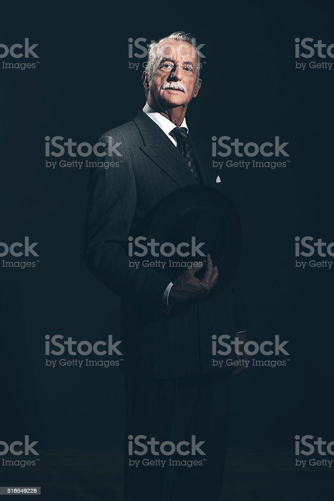 Vintage 40s senior businessman holding hat. Studio shot. stock photo