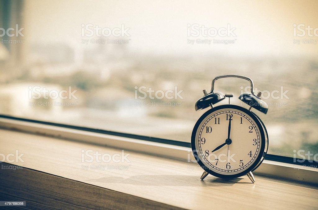 Vintage alarm clock at windows at early morning stock photo