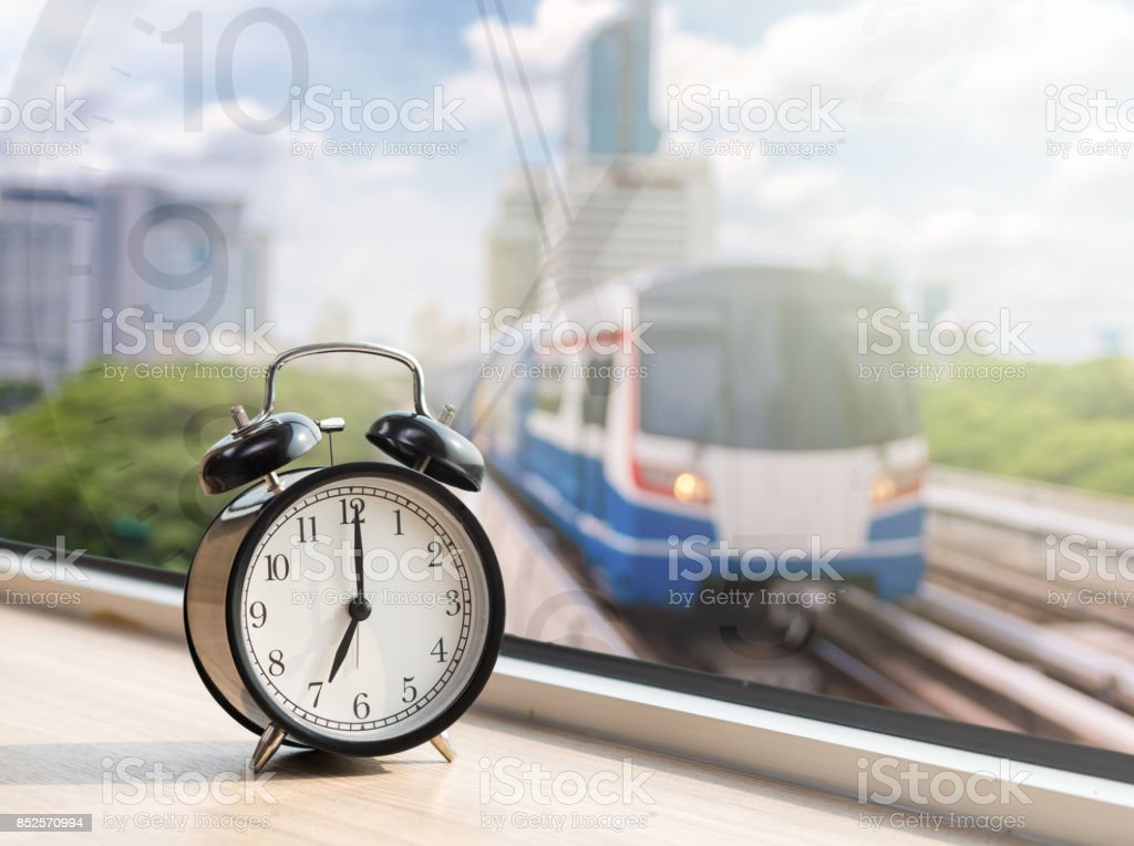 Vintage alarm clock at windows with abstract Blurred photo of sky train with traffic jam on early morning, traffic tranportation concept stock photo