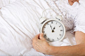 Vintage alarm clock on the bed of senior woman